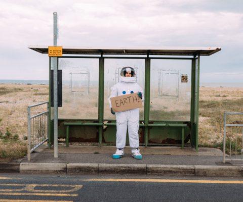 astronaut waiting at a bus stop