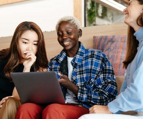 cheerful multiethnic colleagues browsing internet on laptop