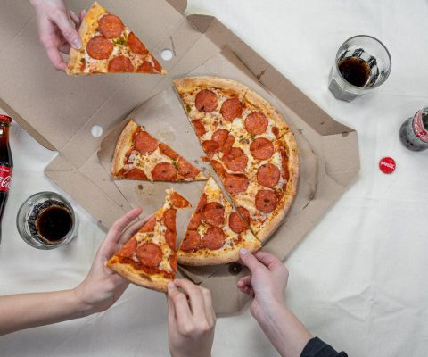 person holding pizza on white box