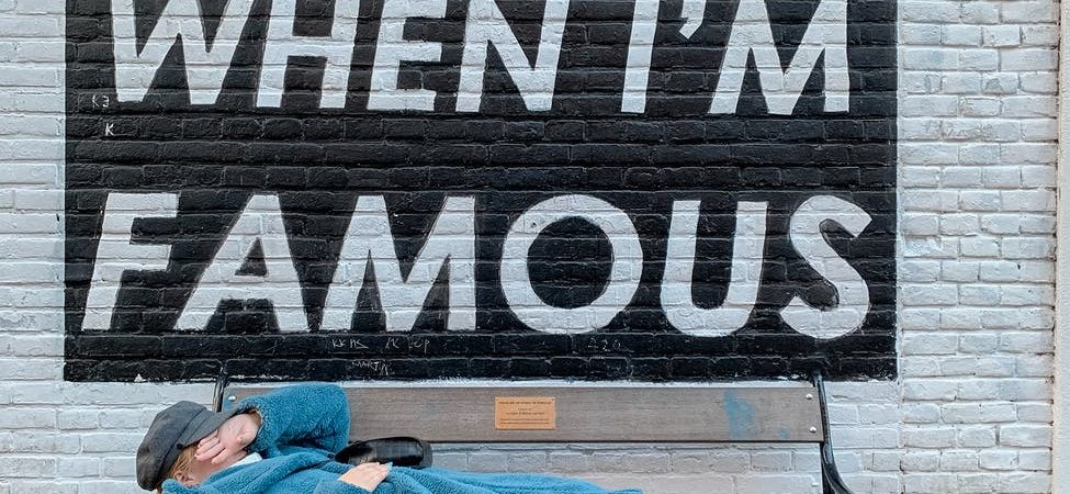 unrecognizable trendy woman lying on street bench near wall with inscription on autumn day