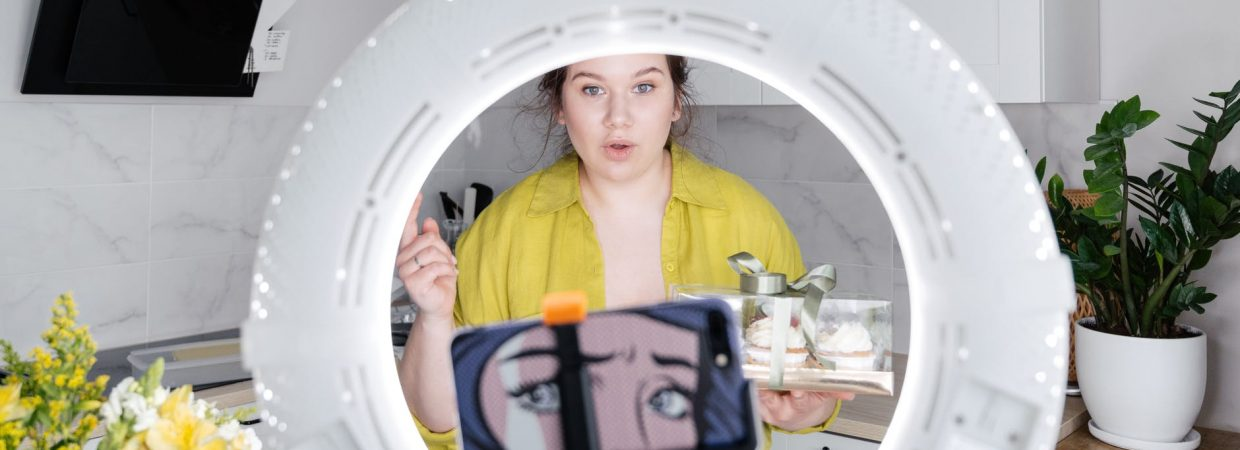 young woman recording new vlog on smartphone in kitchen